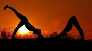Two woman practice yoga outside as the sun goes down